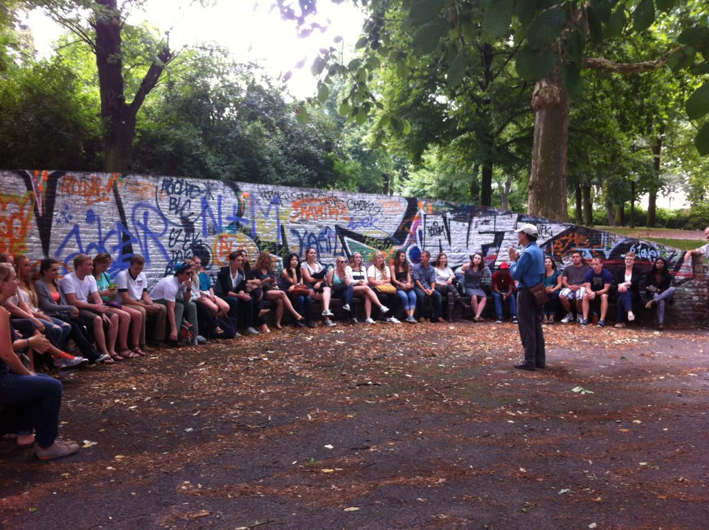 Student lecture in front of a colorful wall