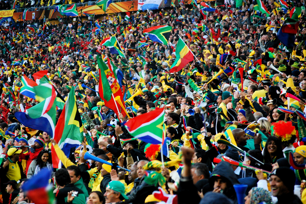 People holding up the South African flag and cheering