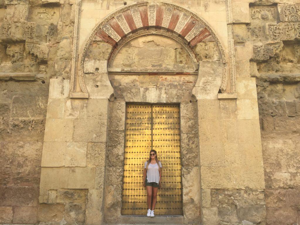 Student in front of gold door