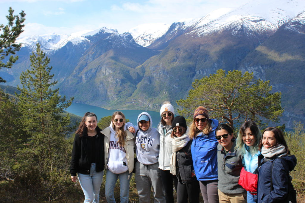 students and staff gather on top of a scenic glacial valley in Norway